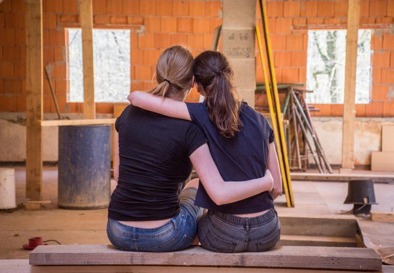 deux filles se prenant dans les bras devant un chantier
