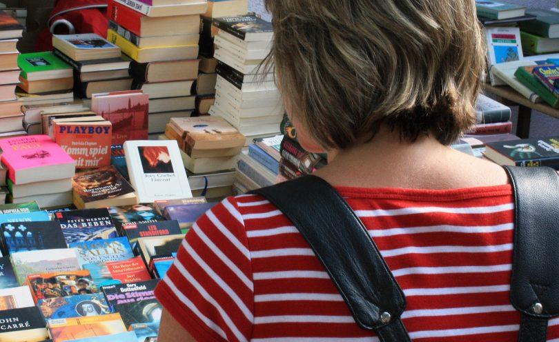 femme regardant un stand de livres