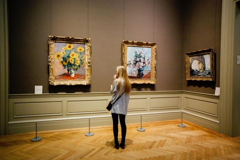 femme regardant des tableaux dans un musée