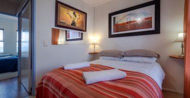 chambre a coucher avec lit et couverture rayée