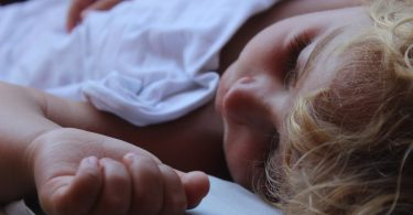 enfant qui dort dans un drap blanc