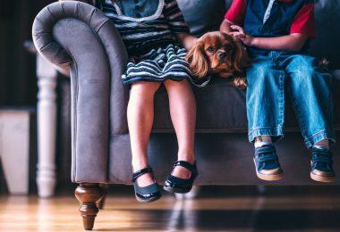 deux enfants avec un chien assis sur un canapé