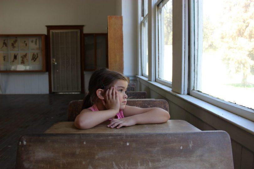 fille assise a une table de classe accoudée et regardant par la fenetre