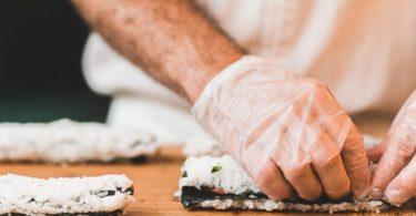 main gantée en train de rouler un sushi