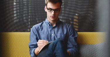 garçon écrivant jambes croisées sur un canapé jaune