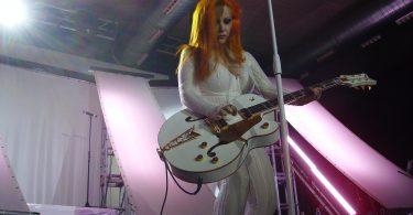 femme rousse en combinaison blanche jouant de la guitare