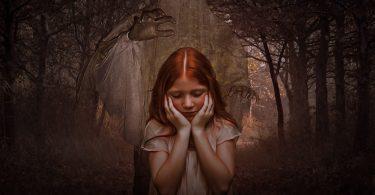 jeune fille rousse se tenant le visage avec les mains autour d'arbres morts