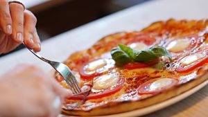 fourchette dans une pizza tomate et fromage