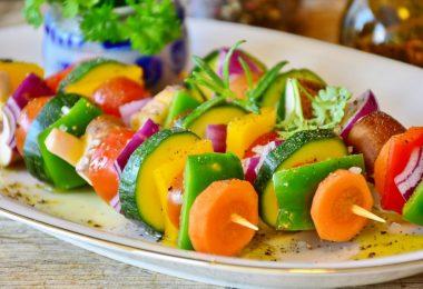trois brochettes de legumes dans une assiette