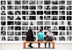 trois personnes assises sur un banc en bois devant des photos en noir et blanc