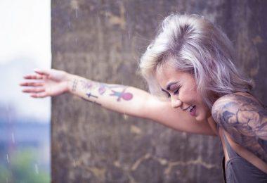 femme souriant avec des tatouages sur le bras