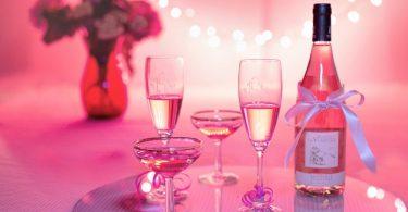 bouteille et duo de coupes de champagne sur fond rose