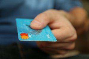 main d'homme tendant une carte bancaire