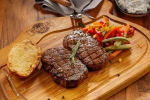 deux morceaux de steak sur une planche en bois
