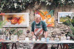 homme peignant sur une table avec des peintures sur le mur en pierre
