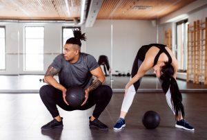 un homme accroupi avec ballon et femme penchée en avant dans une salle de gym