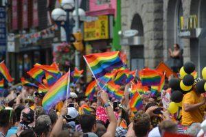 gens dans la rue avec des drapeaux gay