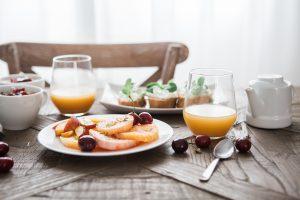 Manger santé Madrid avec jus de fruit et assiette de fruits sur une table