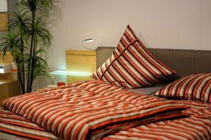 lit d'un hôtel avec des draps rayés orange, noir et blanc