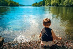 enfant devant un lac dans un parc