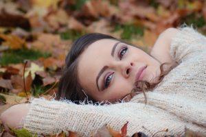 femme allongée dans l'herbe avec des feuilles mortes et un pull blanc