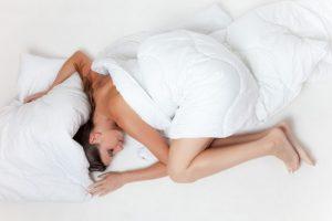 femme nue qui dort dans des draps blancs