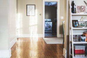 couloir de maison avec plancher en vois et murs beiges