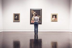 femme devant des peintures dans une salle