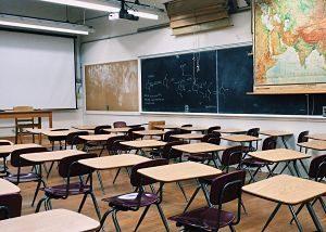 salle de classe avec tables chaises et mur d'ardoise