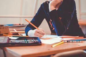 main d'enfant tenant un crayon sur une table