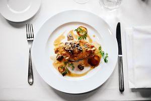 assiette blanche avec de la viande sur une table avec couverts