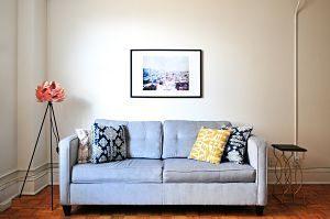 canapé bleu deux places avec coussins colorés et un cadre au mur