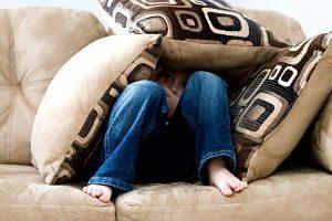 enfant caché sous des coussins sur un canapé