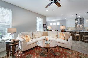 salon avec canapé d'angle, table et ventilateur
