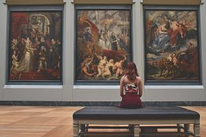 femme assise devant trois peintures