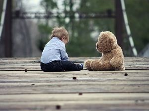 enfant assis devant un ours en peluche