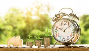reveil-matin et pieces de monnaie avec une maison en bois